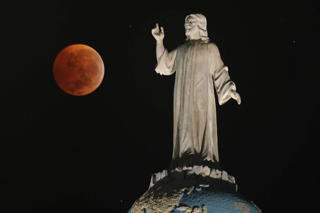 Slide 4 of 53: A double expousure picture shows the moon and the monument of The Savior of The World during a total lunar eclipse as seen from San Salvador, El Salvador on December 21, 2010. This eclipse takes place just hours before the December solstice, which marks the beginning of northern winter and southern summer. AFP PHOTO/ Jose CABEZAS (Photo credit should read Jose CABEZAS/AFP/Getty Images)