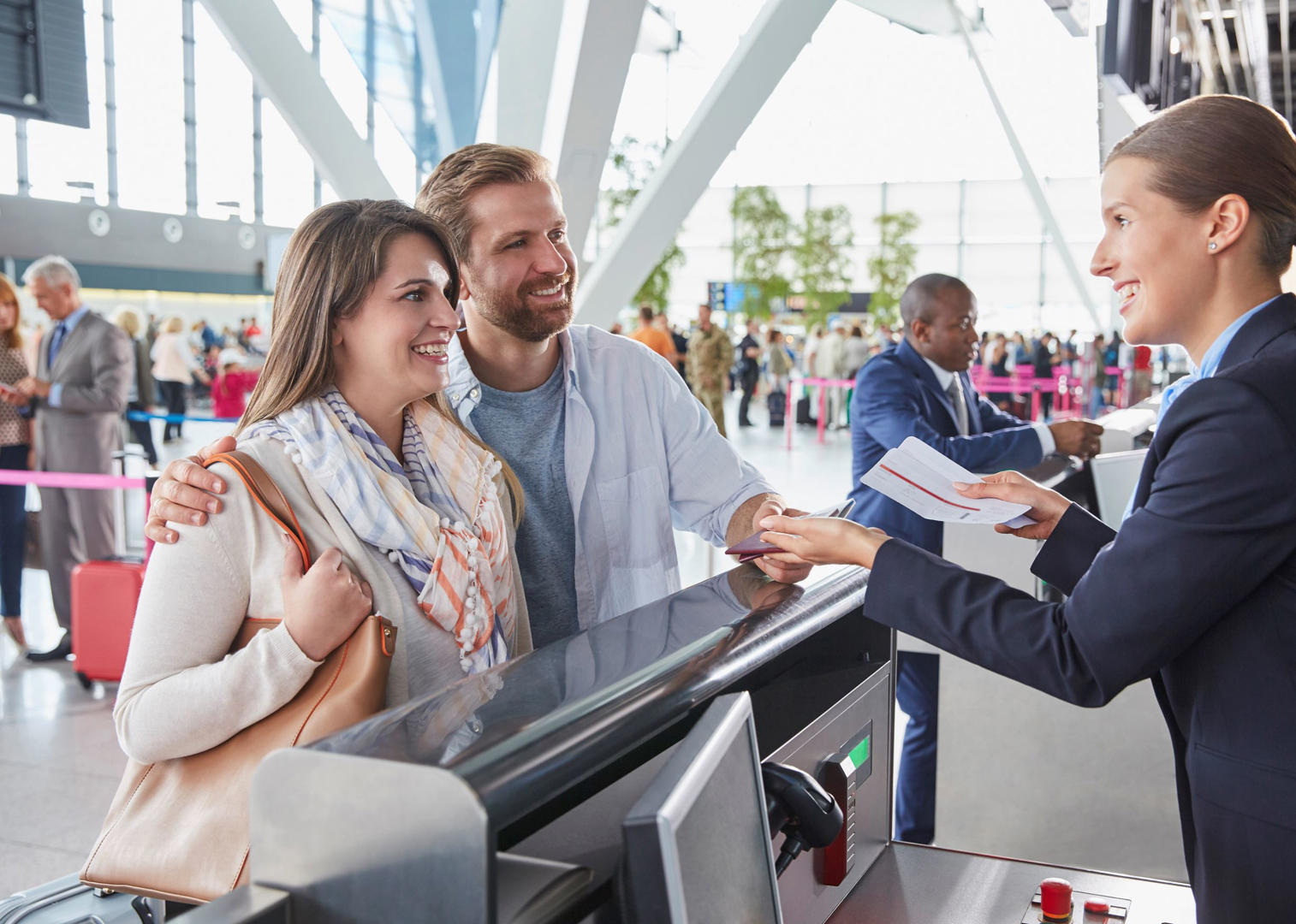 Slide 1 of 9: Customer service representative helping couple at airport check-in counter