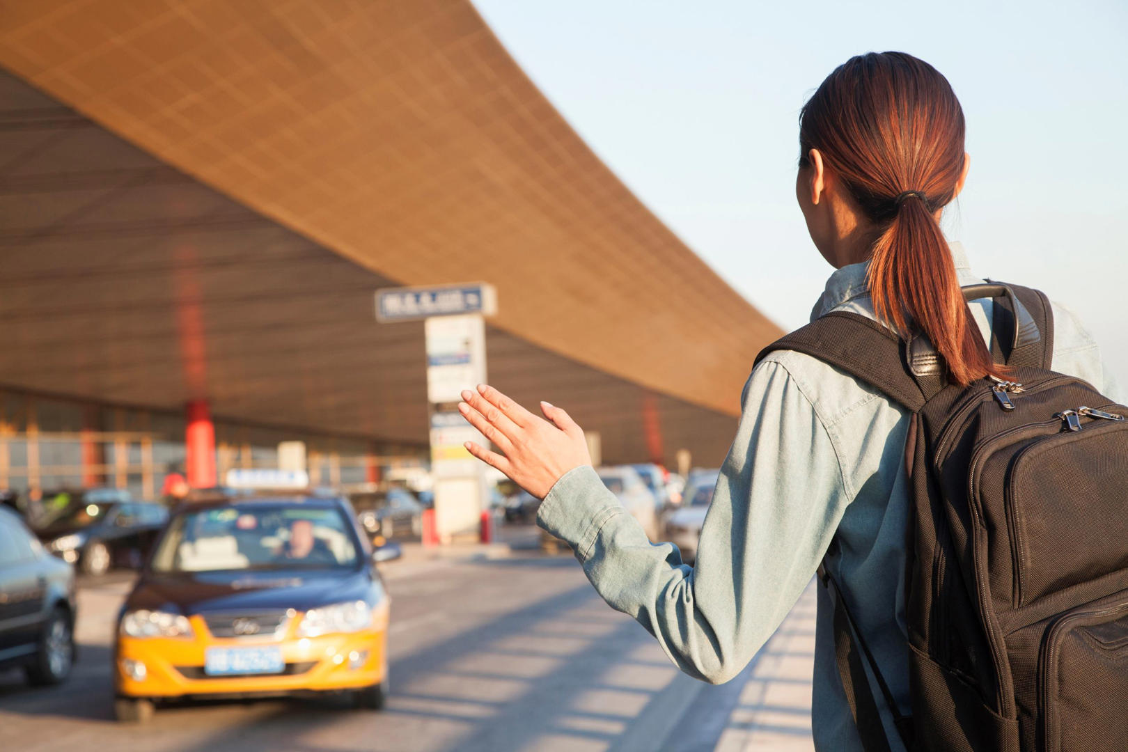 Slide 3 of 9: Young woman getting a taxi in an airport