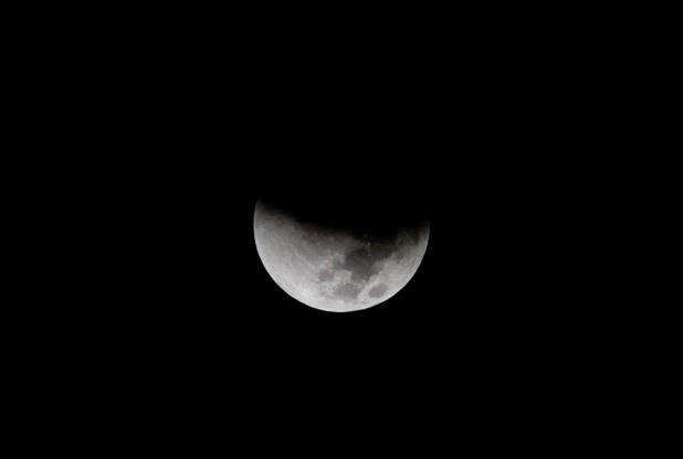 Slide 2 of 53: In this Monday, Sept. 28, 2015 photo, earth's shadow begins to obscure the view of a so-called supermoon during a total lunar eclipse over the Mediterranean Sea in Netanya, Israel. A team of Israeli engineers is the first to advance in an international competition sponsored by Google to send a privately-funded spacecraft to the moon, contest organizers announced Wednesday, Oct. 7. (AP Photo/Ariel Schalit)