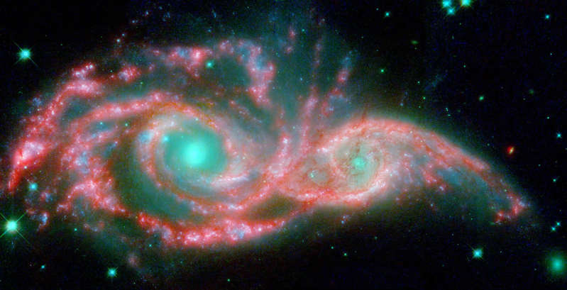 Slide 71 of 86: These shape-shifting galaxies have taken on the form of a giant mask. The icy blue eyes are actually the cores of two merging galaxies, called NGC 2207 and IC 2163, and the mask is their spiral arms. The false-color image consists of infrared data from NASA's Spitzer Space Telescope (red) and visible data from NASA's Hubble Space Telescope (blue/green).  NGC 2207 and IC 2163 met and began a sort of gravitational tango about 40 million years ago. The two galaxies are tugging at each other, stimulating new stars to form. Eventually, this cosmic ball will come to an end, when the galaxies meld into one. The dancing duo is located 140 million light-years away in the Canis Major constellation.  Image Credit: NASA/JPL-Caltech/STScI/Vassar