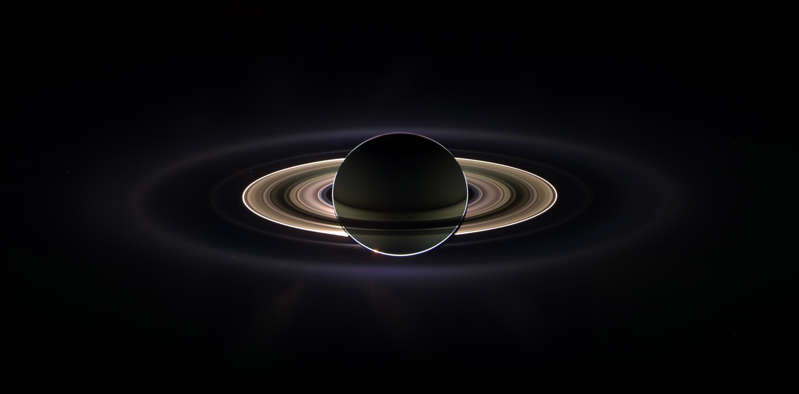 Slide 44 of 86: With giant Saturn hanging in the blackness and sheltering Cassini from the sun's blinding glare, the spacecraft viewed the rings as never before.  This marvelous panoramic view was created by combining a 165 images taken by the Cassini wide-angle camera over nearly three hours on Sept. 15, 2006. The mosaic images were acquired as the spacecraft drifted in the darkness of Saturn's shadow for about 12 hours, allowing a multitude of unique observations of the microscopic particles that comprise Saturn's faint rings.  The narrowly confined G ring is easily seen here, outside the bright main rings. Encircling the entire system is the much more extended E ring. The icy plumes of Enceladus, whose eruptions supply the E ring particles, betray the moon's position in the E ring's left side edge.  Interior to the G ring and above the brighter main rings is the pale dot of Earth. Cassini views its point of origin from close to a billion miles away in the icy depths of the outer solar system.  Image Credit: NASA/JPL/Space Science Institute