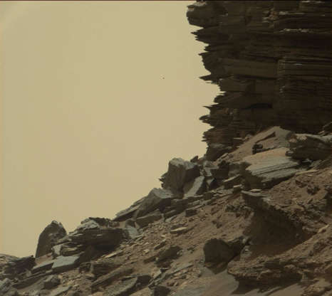 """Slide 27 of 86: This view from the Mast Camera (Mastcam) in NASA's Curiosity Mars rover shows a hillside outcrop with layered rocks within the """"Murray Buttes"""" region on lower Mount Sharp. The buttes and mesas rising above the surface in this area are eroded remnants of ancient sandstone that originated when winds deposited sand after lower Mount Sharp had formed. Curiosity closely examined that layer -- called the """"Stimson formation"""" -- during the first half of 2016, while crossing a feature called """"Naukluft Plateau"""" between two exposures of the Murray formation. The layering within the sandstone is called """"cross-bedding"""" and indicates that the sandstone was deposited by wind as migrating sand dunes. The image was taken on Sept. 8, 2016, during the 1454th Martian day, or sol, of Curiosity's work on Mars."""