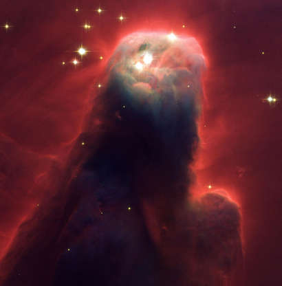 Slide 49 of 86: Resembling a nightmarish beast rearing its head from a crimson sea, this monstrous object is actually an innocuous pillar of gas and dust. Called the Cone Nebula (NGC 2264) ? so named because, in ground-based images, it has a conical shape ? this giant pillar resides in a turbulent star-forming region. This picture, taken by the newly installed Advanced Camera for Surveys (ACS) aboard NASA's Hubble Space Telescope, shows the upper 2.5 light-years of the nebula, a height that equals 23 million roundtrips to the Moon. The entire nebula is 7 light-years long. The Cone Nebula resides 2,500 light-years away in the constellation Monoceros (Photo by NASA/WireImage) *** Local Caption ***