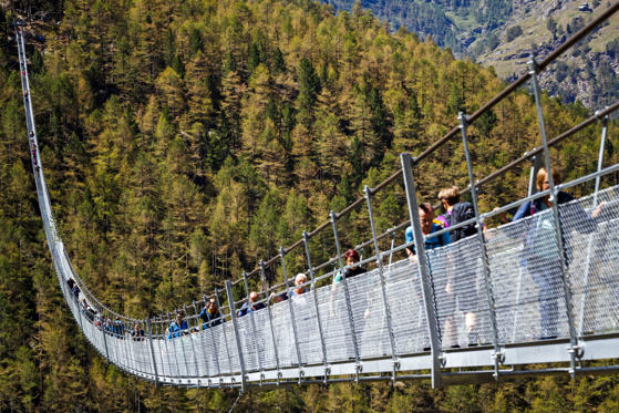 Slide 1 of 19: People walk on the 'Europabruecke' bridge, the world's longest pedestrian suspension bridge with a length of 494m, after the official inauguration of the construction in Randa, Switzerland, 29 July 2017. The bridge is situated on the Europaweg that connects the villages of Zermatt and Graechen.