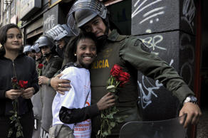 A riot policeman hugs an activist who gave him a rose during the National Day of Remembrance and Solidarity with Victims of the Armed Conflict, in Bogota, Colombia on April 9, 2014. In Colombia, the armed conflict which involved leftist guerrillas, right-wing paramilitaries, military and drug gangs has left 6 million affected, of which at least 5 million are displaced according to the most recent UN human rights report. AFP PHOTO / Guillermo Legaria (Photo credit should read GUILLERMO LEGARIA/AFP/Getty Images)