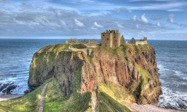 Slide 1 of 27: Perched on a headland jutting into the North Sea, Dunnottar Castle is best known as the place where the Scottish crown jewels – the Honours of Scotland – were hidden when Oliver Cromwell invaded Scotland in 1650. The oldest buildings date from the 14th century.