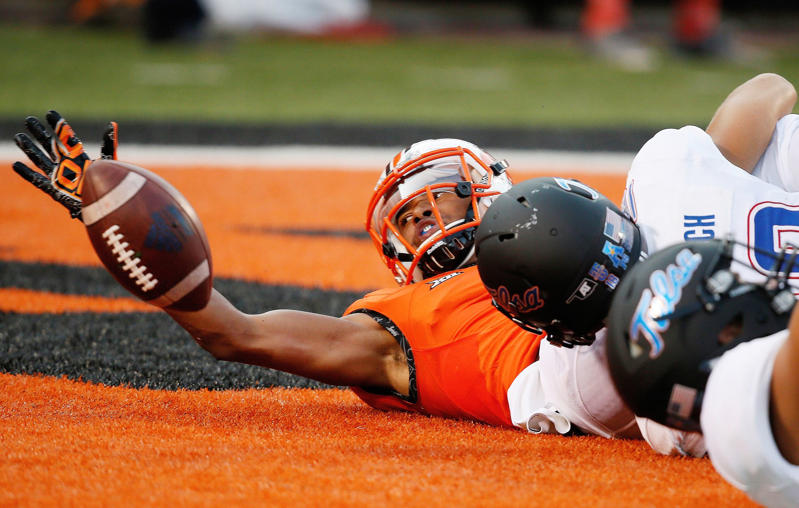 Oklahoma State wide receiver Jalen McCleskey (1) reaches for the ball in front of Tulsa safety Samuel Gottsch (18) following a fumble on a kick return in Stillwater, Okla. on Aug. 31. Oklahoma State won 59-24.