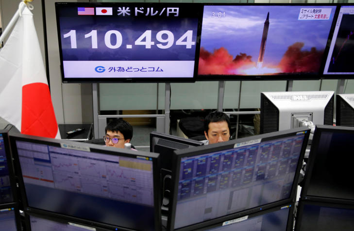 Employees of a foreign exchange trading company work in front of monitors showing TV news on North Korea's threat (R) and the Japanese yen's exchange rate against the U.S. dollar (L) in Tokyo, Japan, September 14, 2017.