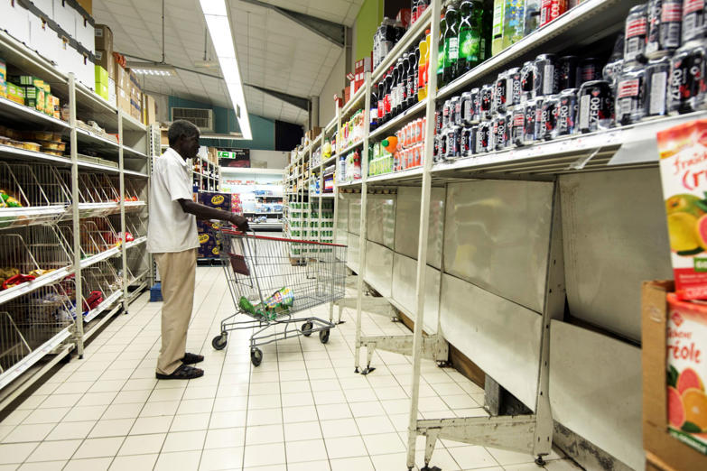 Slide 46 of 46: A man pushes a shoppping trolley in a supermarket where all packs of bottled water have been sold, in Pointe-a-Pitre, on the French overseas island of Guadeloupe on September 4, 2017, as part of preparations for arrival of Hurricane Irma.