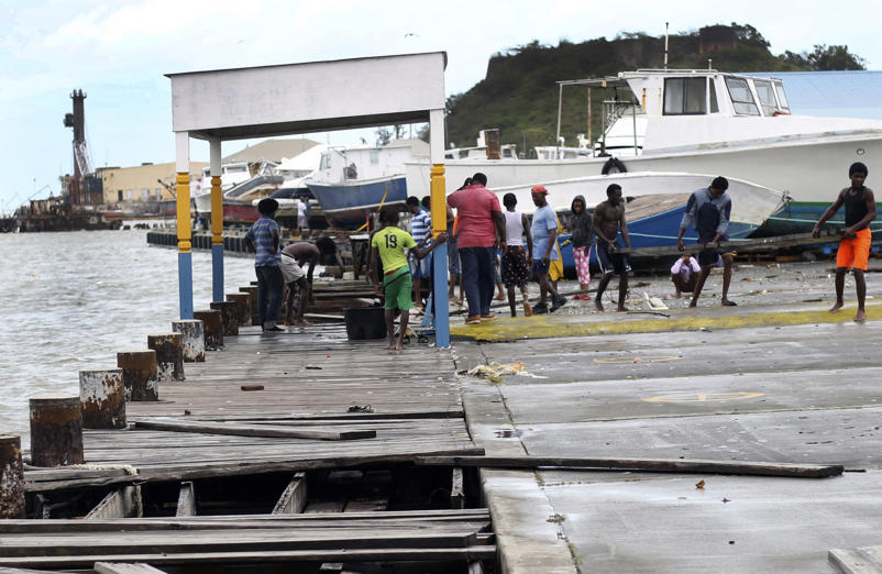 Slide 25 of 31: People recover broken parts of the dock after the passing of Hurricane Irma, in St. John's, Antigua and Barbuda, Wednesday, Sept. 6, 2017. Heavy rain and 185-mph winds lashed the Virgin Islands and Puerto Rico's northeast coast as Irma, the strongest Atlantic Ocean hurricane ever measured, roared through Caribbean islands on its way to a possible hit on South Florida. (AP Photo/Johnny Jno-Baptiste)