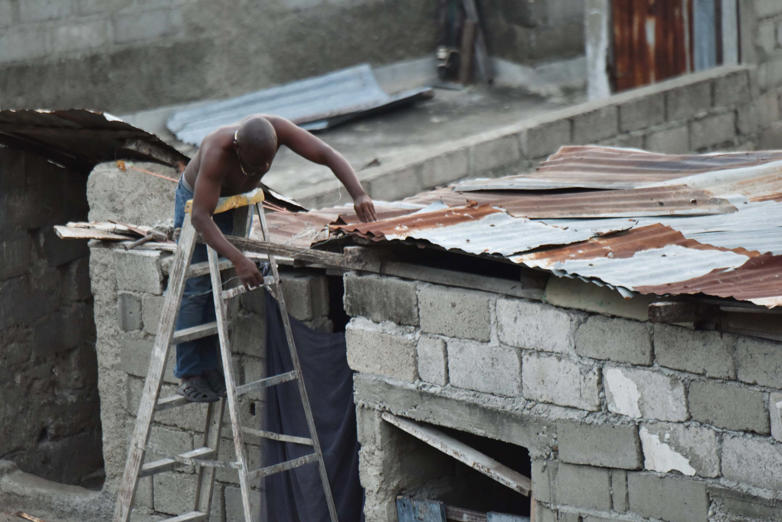 Slide 4 of 46: A man repairs a part of his roof in preparation for the arrival of Hurricane Irma in Lauriers neighborhood of Cap-Haitien, on September 6, 2017, 240 km from Port-au-Prince. / AFP PHOTO / HECTOR RETAMAL        (Photo credit should read HECTOR RETAMAL/AFP/Getty Images)