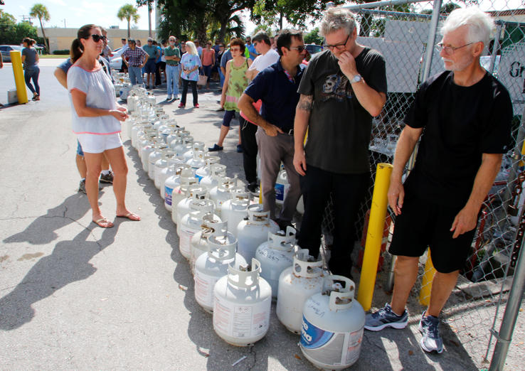 Slide 3 of 46: Residents wait in line to purchase propane gas at Lee's Barbecue Center in Boca Raton, Florida, as they  continue to prepare for Hurricane Irma's expected arrival, September 6, 2017.  Residents. REUTERS/Joe Skipper - RC160ECE4AD0