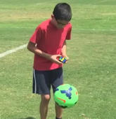 Boy solves Rubik's Cube while juggling soccer ball