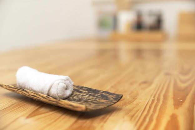 21 枚のスライドの 15 枚目: Shallow DOF of refreshing towel on top of wooden plate over japanese restaurant wooden table
