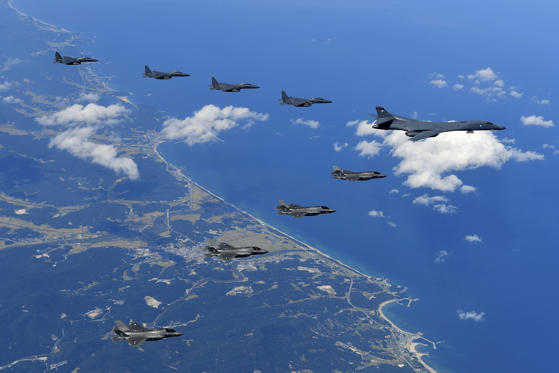 Slide 10 of 79: In this handout image provided by South Korean Defense Ministry, U.S. Air Force B-1B Lancer bombers flying with F-35B fighter jets and South Korean Air Force F-15K fighter jets during a training at the Pilsung Firing Range on September 18, 2017 in Gangwon-do, South Korea. U.S. F-35B stealth jets and B-1B bombers flew near the Military Demarcation Line (MDL) for the first time since recent tension between U.S. and North Korea started raising.