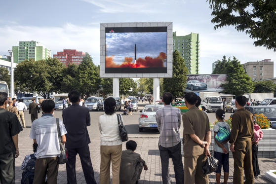 """Slide 13 of 79: People watch as a screen shows footage of the launch of a Hwasong-12 rocket, beside a billboard advertising North Korea's Pyeonghwa Motors (R), in Pyongyang on September 16, 2017. North Korea said on September 16 it was seeking military """"equilibrium"""" with the United States as leader Kim Jong-Un vowed to complete Pyongyang's nuclear programme."""
