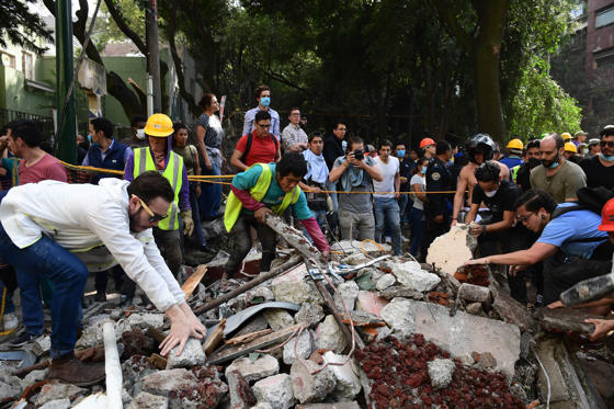 Slide 8 of 42: Rescuers look for survivors in a multistory building flattened by a powerful quake in Mexico City on September 19, 2017. A devastating quake in Mexico on Tuesday killed more than 100 people, according to official tallies, with a preliminary 30 deaths recorded in the capital where rescue efforts were still going on. / AFP PHOTO / RONALDO SCHEMIDT        (Photo credit should read RONALDO SCHEMIDT/AFP/Getty Images)