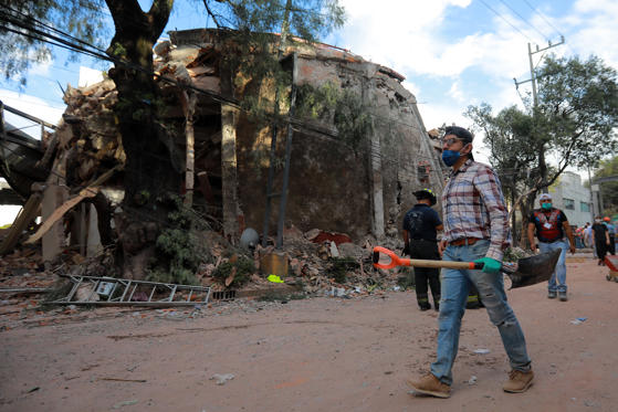 Slide 3 of 42: MEXICO CITY, MEXICO - SEPTEMBER 19: A man carries a shovel and gloves as he looks for victims amid the ruins of a building knocked down by a magnitude 7.1 earthquake that jolted central Mexico damaging buildings, knocking out power and causing alarm throughout the capital on September 19, 2017 in Mexico City, Mexico. The earthquake comes 32 years after a magnitude-8.0 earthquake hit on September 19, 1985. (Photo by Hector Vivas/Getty Images)