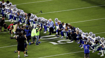 The Cowboys, led by owner Jerry Jones, center, take a knee prior to the national anthem before the game against the Cardinals, on Sept. 25 in Glendale, Ariz.