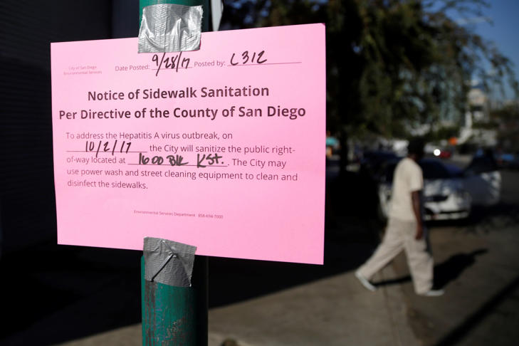 In this Sept. 28, 2017 file photo a man passes behind a sign warning of an upcoming street cleaning in San Diego. Health officials say a deadly California outbreak of hepatitis A may take a year or more to abate.