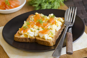 Toasted bread topped with smoked salmon and scrambled eggs