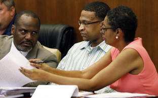 Defense attorneys Alton Peterson, left, and Darla Palmer, right, consult with their client, Quinton Tellis, 29, who is charged with burning 19-year-old Jessica Chambers, to death almost three years ago, during closing arguments in his capital murder trial in a courtroom in Batesville, Miss., Sunday, Oct. 15, 2017.