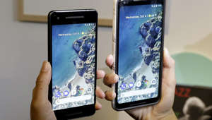 A woman holds up the Google Pixel 2 phone, left, next to the Pixel 2 XL phone