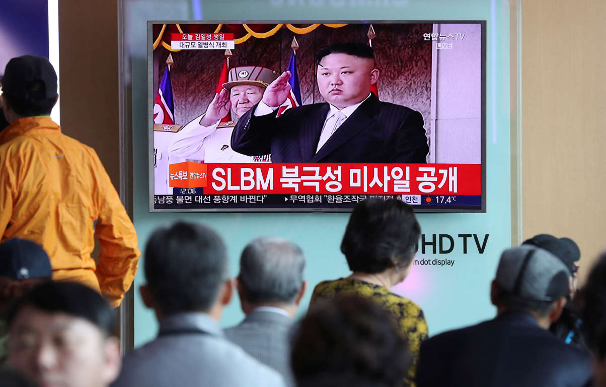 People watch a live television program showing North Korean leader Kim Jong Un salutes during a parade in Pyongyang, North Korea, at the Seoul train station in Seoul, South Korea, Saturday, April 15, 2017.