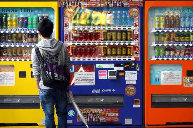 21 枚のスライドの 7 枚目: People purchase bottle drinks from a vending machine on Feb. 12, 2015 in Tokyo, Japan. Around half of the vending machines in Japan sell drinks, and this has led to the development of proprietary technology such as that which enables both gattakaih (hot) and gtsumetaih (cool) drinks to be housed inside the same vending machine.