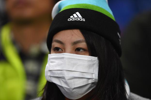 21 枚のスライドの 3 枚目: A fan wears a protective mask during the FIFA Club World Cup second round match between Jeonbuk Hyundai and Club America at Suita City Football Stadium on December 11, 2016 in Suita, Japan.