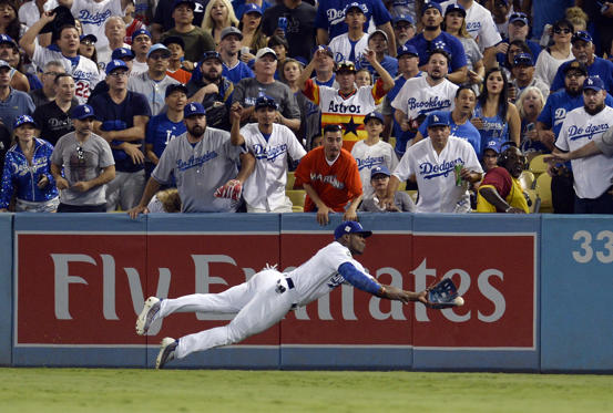 Slide 26 of 39: Dodgers' right fielder Yasiel Puig cannot catch a ball hit for a double by Astros third baseman Alex Bregman in the 8th inning in game two of the 2017 World Series in Los Angeles. Astros won 7-6. Gary A.