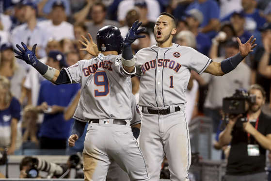 Slide 25 of 39: Marwin Gonzalez (9) of Astros celebrates with Carlos Correa (1) after hitting a solo home run during the ninth inning against Dodgers in game two of the 2017 World Series on Oct. 25 in Los Angeles.