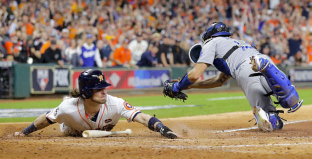 Slide 16 of 39: Astros' Josh Reddick slides safely past Dodgers catcher Austin Barnes during the fifth inning of Game 3 of World Series on Oct. 27 in Houston. Reddick scored on a ball hit by Evan Gattis. Houston won 5-3.