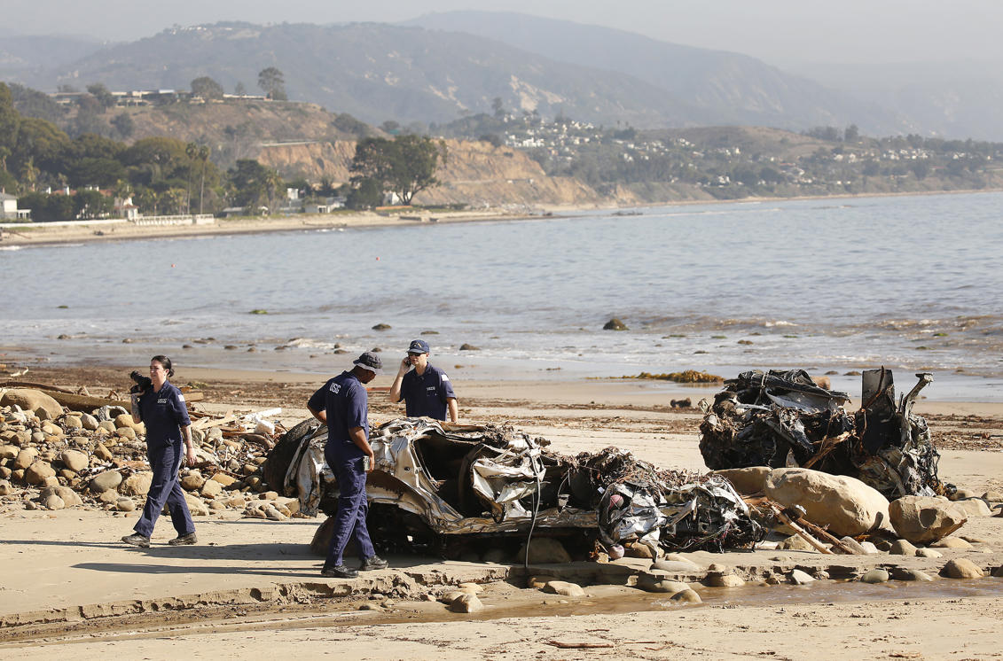 Slide 20 of 78: MONTECITO, CA - JANUARY 11:  Alisha Kleinman, Steve Knight, and Brett Weideman, left to right, members of the US Coast Guard  inspect two crushed vehicles, a Hummer and a Honda that were found on the beach January 11, 2018 after a rainstorm sent mud and debris through Montecito neighborhoods. (Photo by Al Seib/Los Angeles Times via Getty Images)