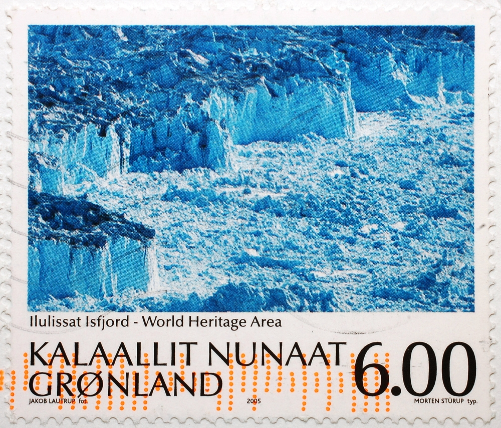 Slide 12 of 70: A stamp printed in Greenland shows image of Ilulissat Isfjord, the World Heritage Area, circa 2005