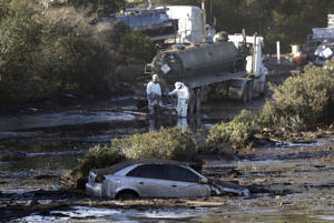Crews pump mud on Highway 101 after a mudslide Saturday, Jan. 13, 2018, in Montecito, Calif.  Most of the people of Montecito, a town usually known for its serenity and luxury, were under orders to stay out of town as gas and power were expected to be shut off Saturday for repairs.