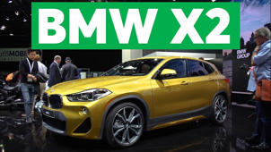 a car parked in front of a sign: 2018 Detroit Auto Show: 2018 BMW X2 is Small and Sporty