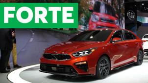 a car parked in front of a sign: 2018 Detroit Auto Show: 2019 Kia Forte Promises Better Fuel Economy, More Room