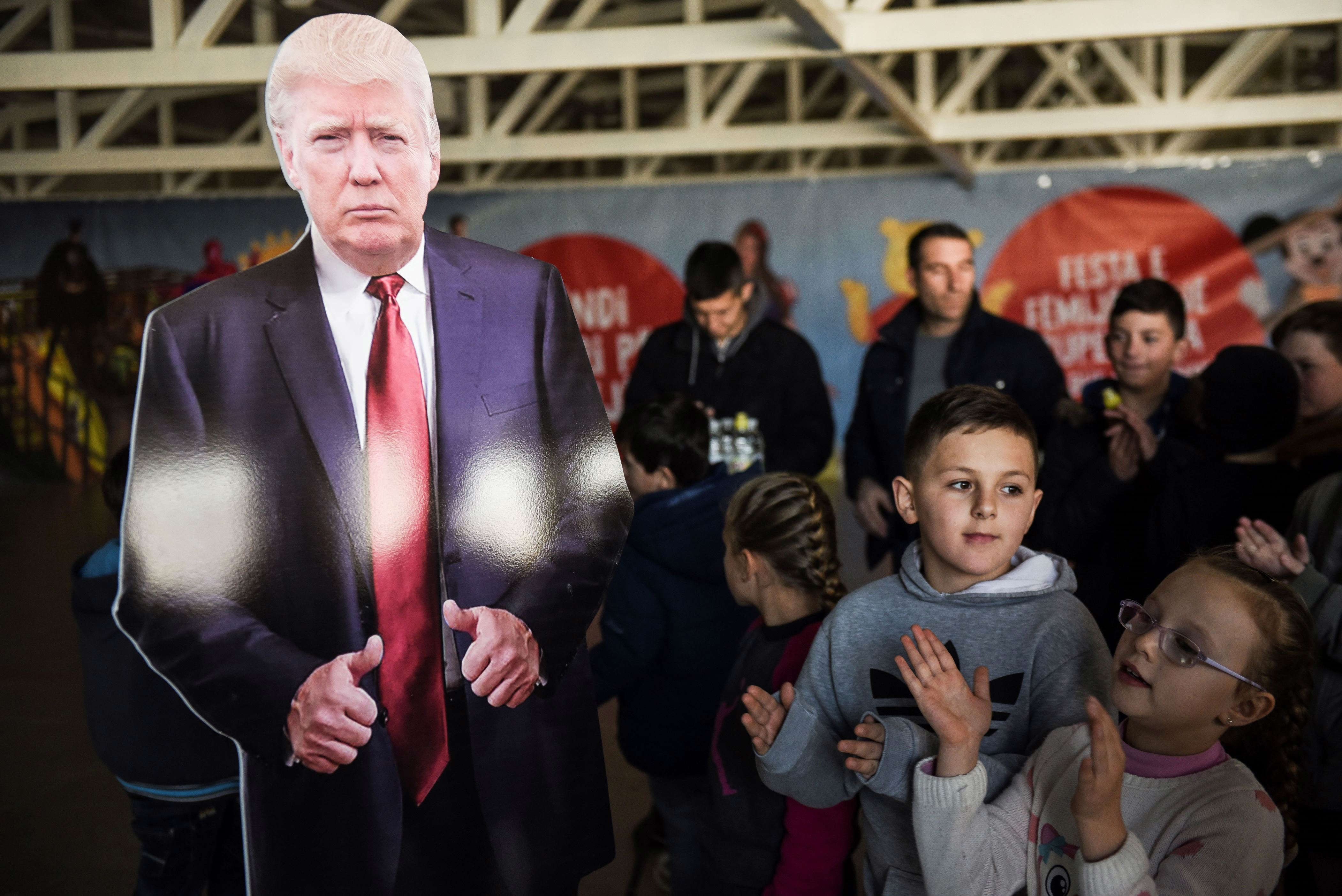 Slide 20 of 35: Children applaud  next to a cardboard depicting U.S President Donald Trump at a restaurant near the town of Ferizaj on January 28, 2017, where  45 pizzas were given for free in honor to the new elected  President of the United States of America. / AFP / Armend NIMANI        (Photo credit should read ARMEND NIMANI/AFP/Getty Images)