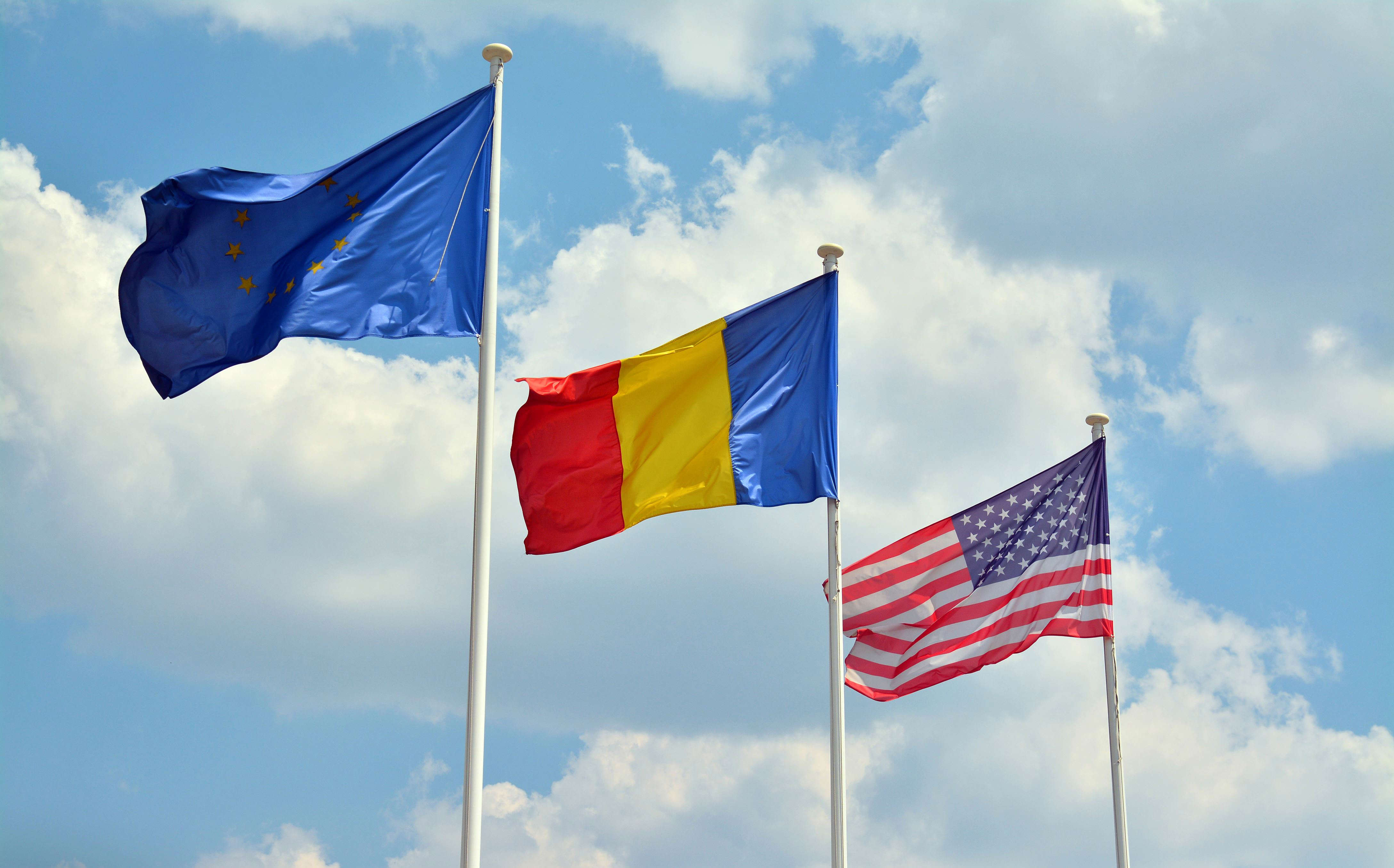 Slide 6 of 35: european union, romanian and american flags waving in the wind