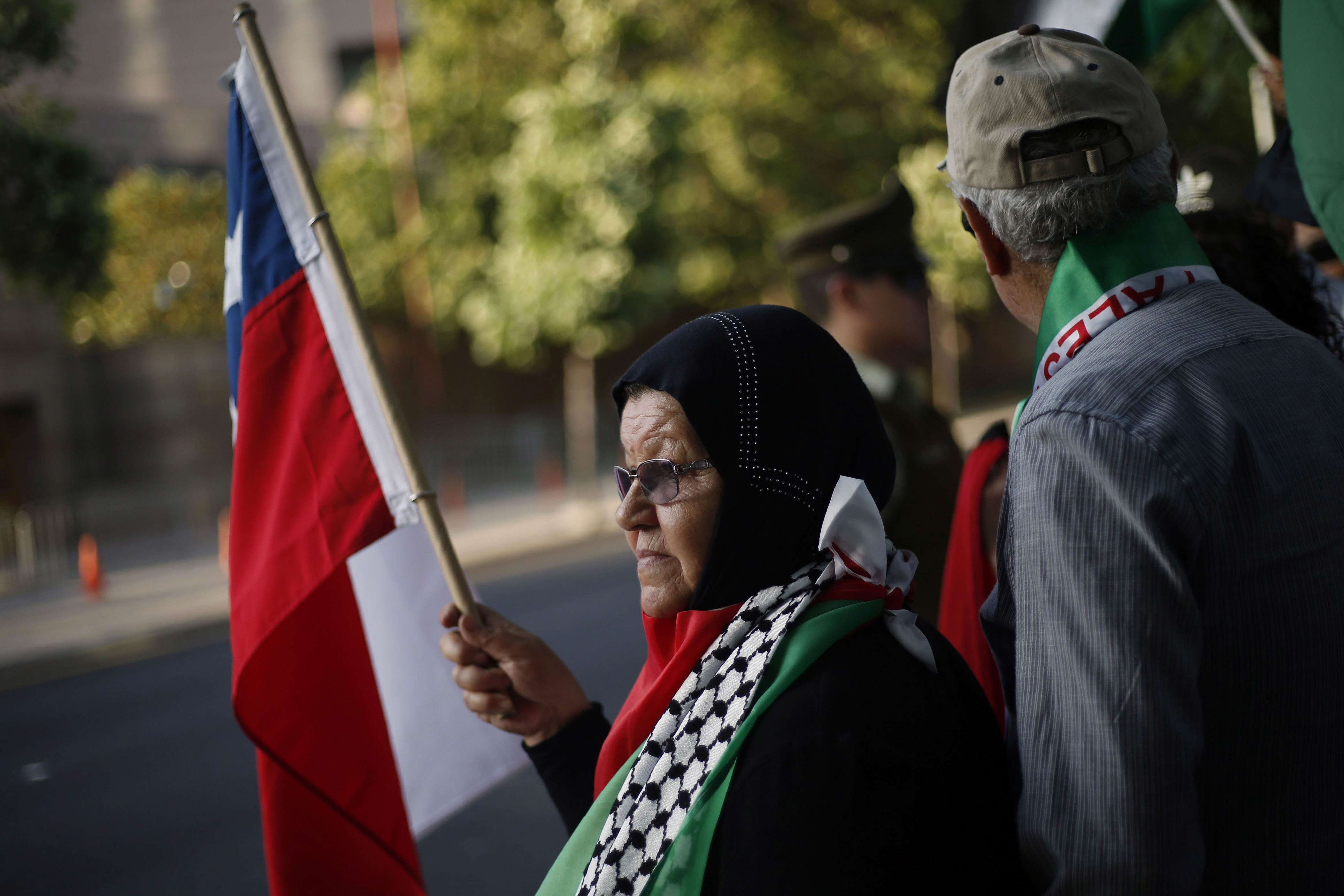 Slide 31 of 35: Chilean supporters of Palestine and Palestinians protest against U.S. President Donald Trump's recognition of Jerusalem as the capital of Israel, in front of the United States embassy in Santiago on December 11, 2017. / AFP PHOTO / Pablo VERA        (Photo credit should read PABLO VERA/AFP/Getty Images)