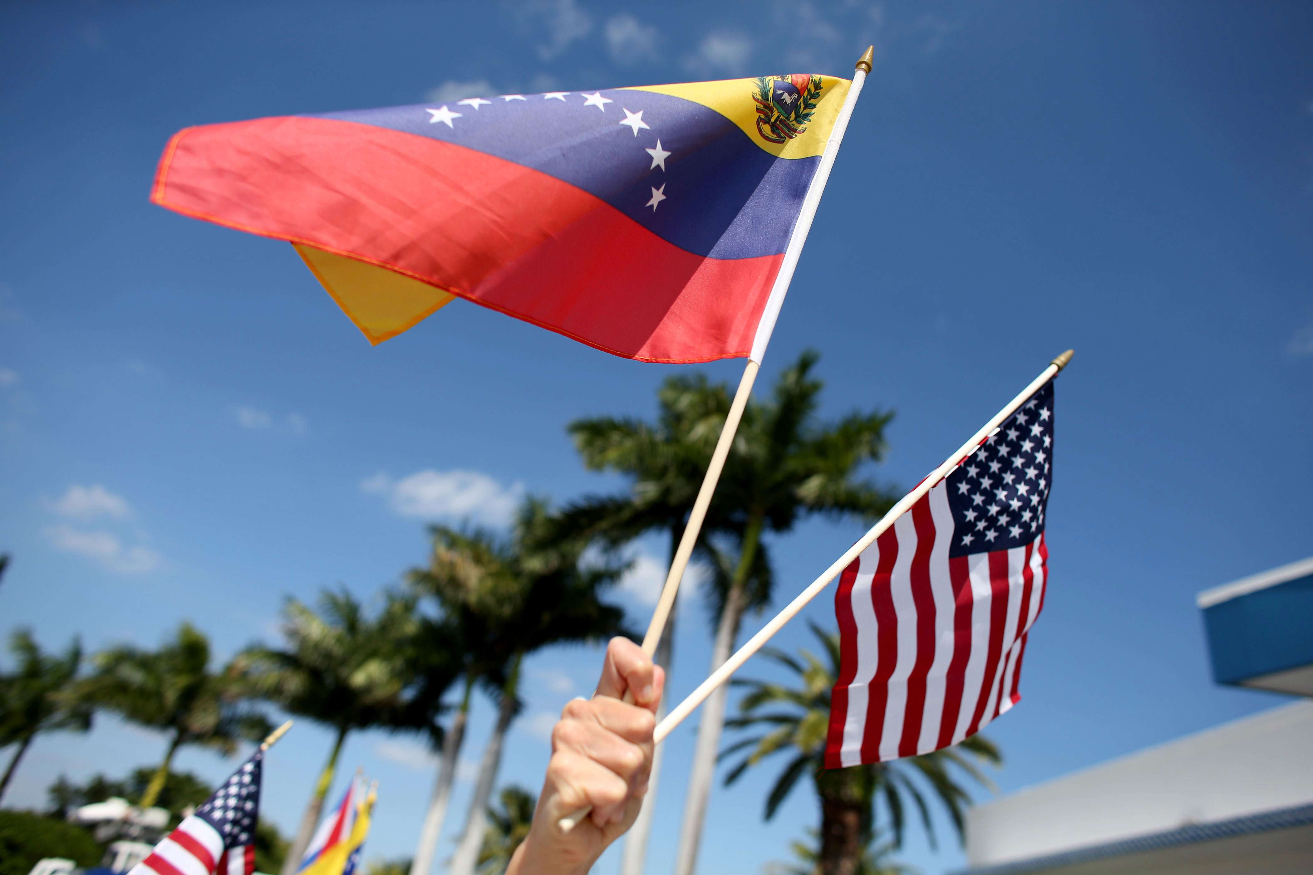 Slide 5 of 35: MIAMI, FL - MARCH 01:  A protester holds a Venezuelan and American flag as she and other Venezuelans and their supporters show their support for the anti-government protests in Venezuela on March 1, 2014 in Miami, Florida. In Venezuela, protests over the past couple of weeks have resulted in violence as government opponents and supporters have faced off in the streets.  (Photo by Joe Raedle/Getty Images)