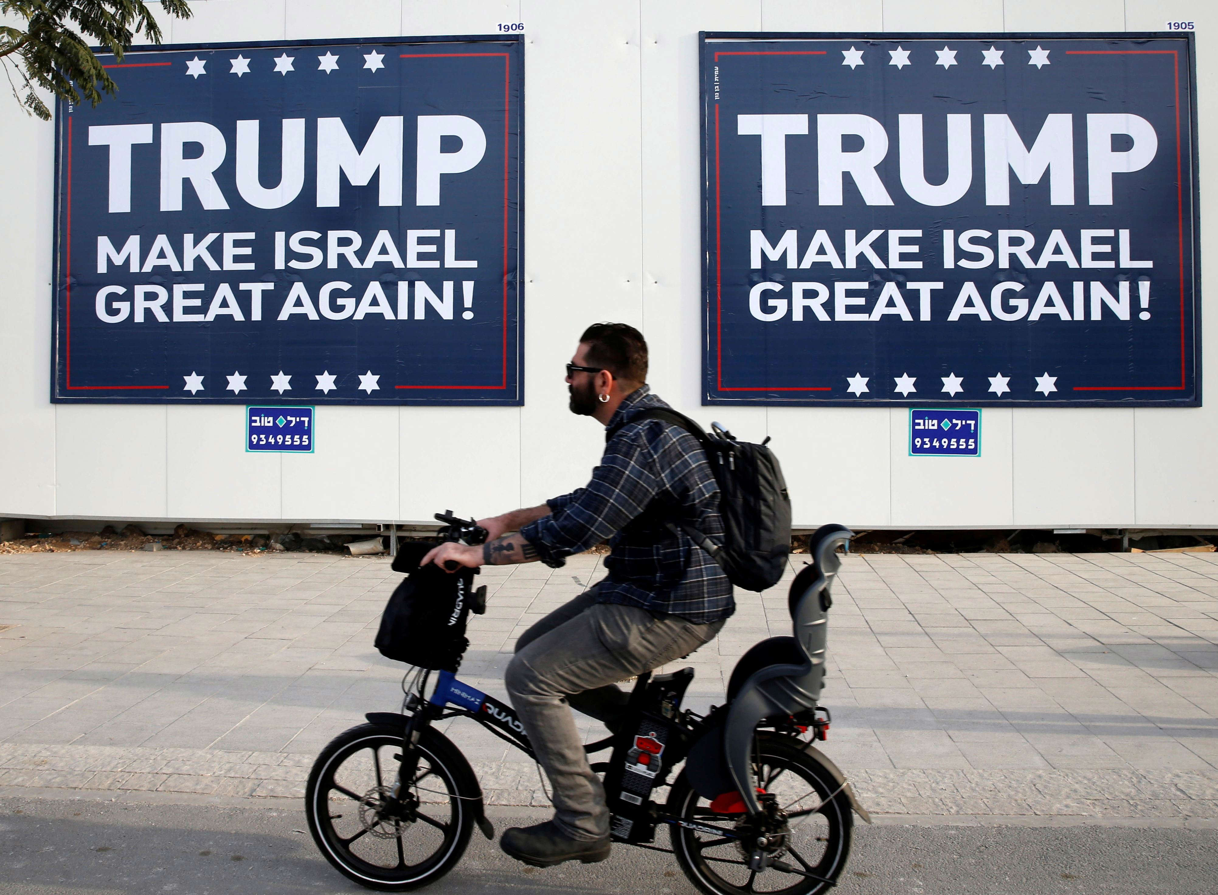 Slide 15 of 35: A man cycles past signs bearing the name of U.S. President-elect Republican Donald Trump in Tel Aviv, Israel November 14, 2016. REUTERS/Baz Ratner      TPX IMAGES OF THE DAY