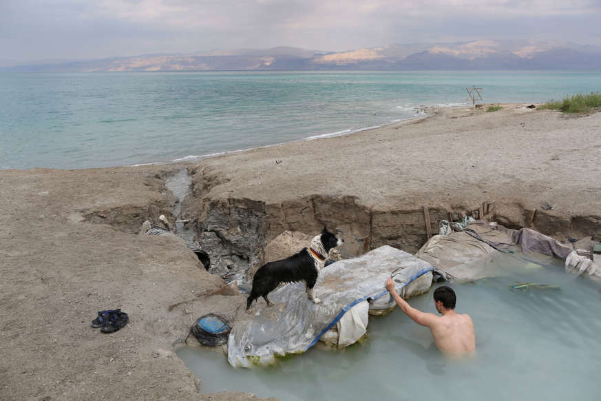 Slide 4 of 25: In this April 2, 2017 photo, a man bathes in a spring water pool along the Dead Sea shore near the Israeli Kibbutz of Ein Gedi. The Dead Sea, a marvel of the natural world, is shrinking. (AP Photo/Oded Balilty)