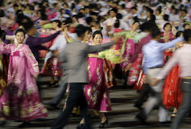 North Korean men and women participate in a mass dance