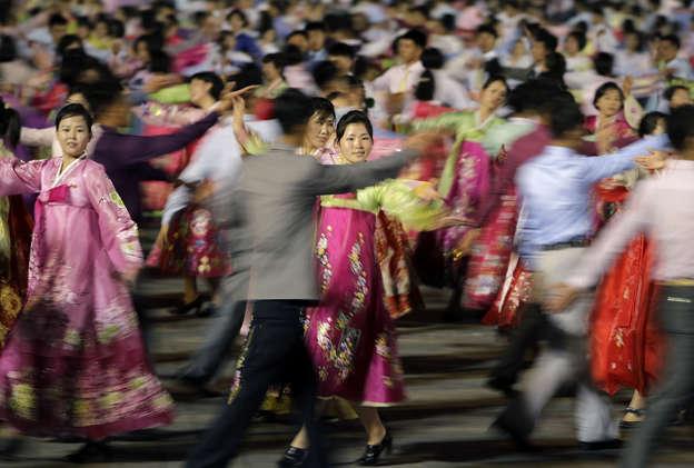 North Korean men and women participate in a mass dance