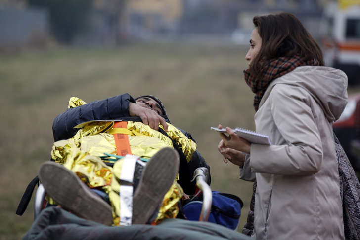A passenger on a stretcher talks to a woman after being rescued from a derailed train, in Pioltello Limito, on the outskirts of Milan, Italy