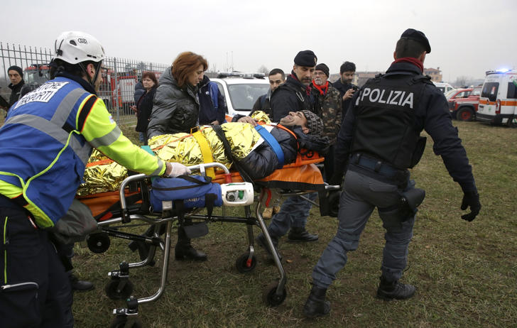 An injured passenger is assisted after a train derailed at the station of Pioltello Limito, on the outskirts of Milan, Italy