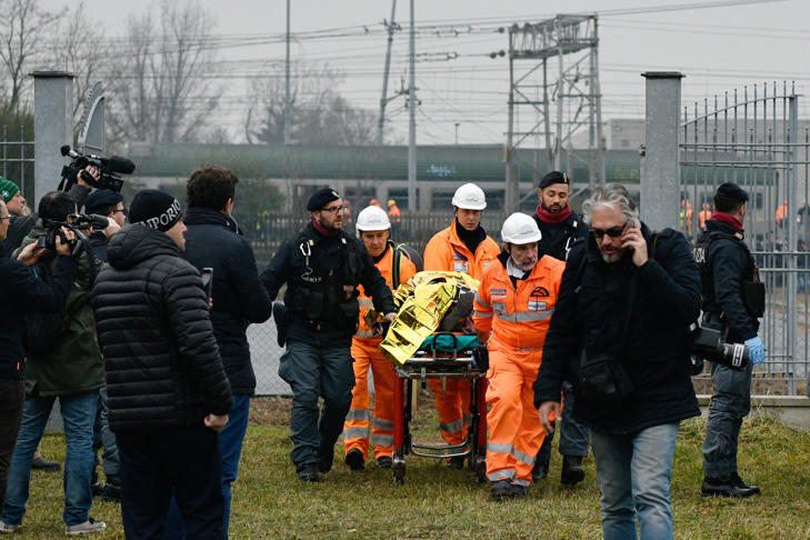 Italian rescuers transport a victim on a stretcher on the site of a train derailment, on January 25, 2018 near Milan.